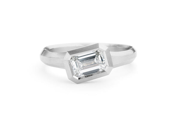 Arris carved platinum engagement ring with emerald-cut white diamond