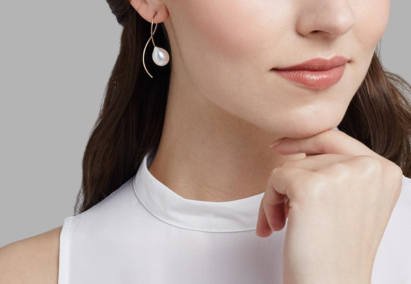 Contemporary white pearl drop earrings on model