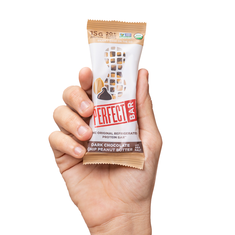 Hand holding Dark Chocolate Chip Peanut Butter bar