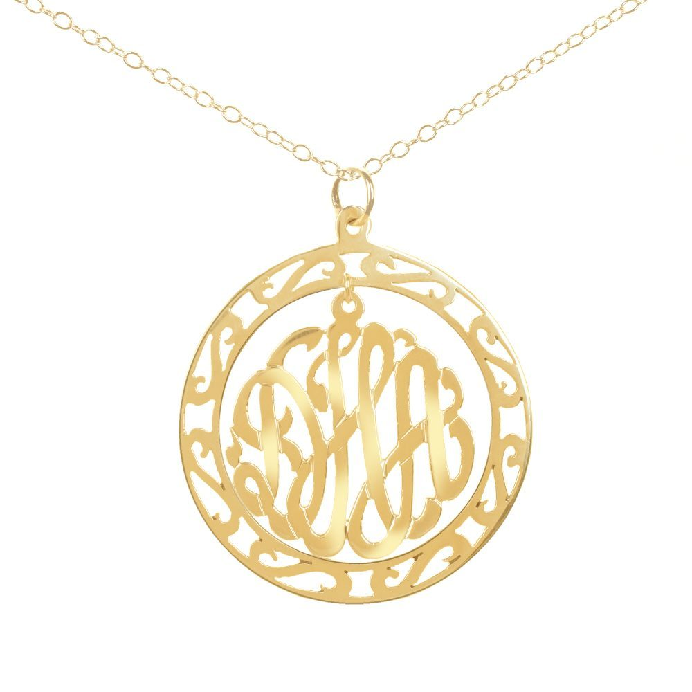 24k gold round monogram necklace hanging inside a hollow patterned circle pendant
