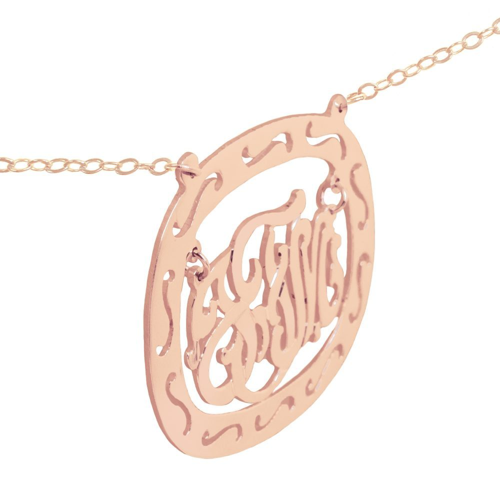 24k rose gold-plated silver oval monogram necklace inside thick patterned circular frame Angle