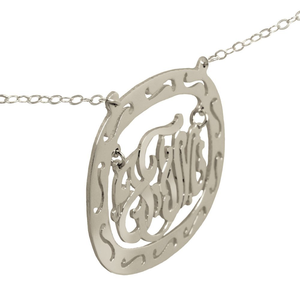 silver oval monogram necklace inside thick patterned circular frame Angle