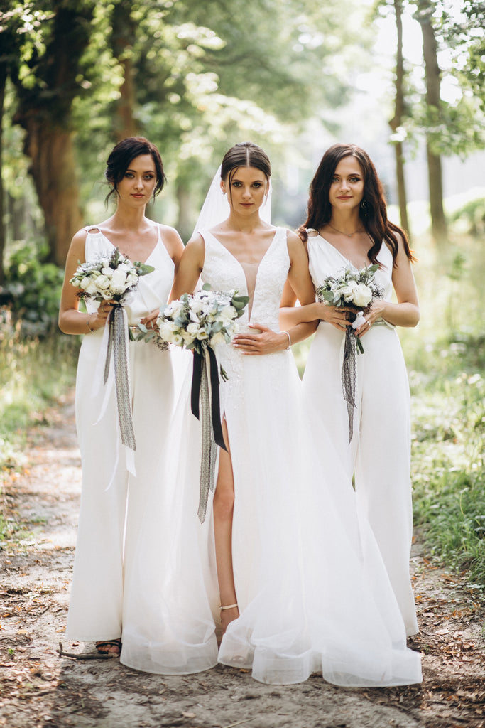 Beautiful bride and bridesmaids in white dresses for elegant garden wedding