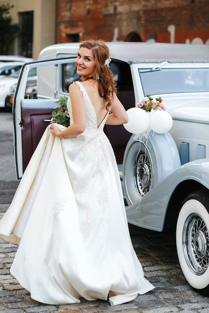 Beautiful bride getting into vintage blue car