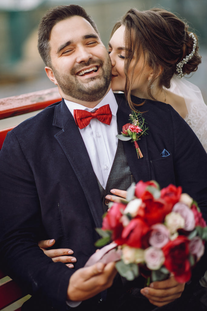 bride and groom in with red floral bouquet kiss on the cheek