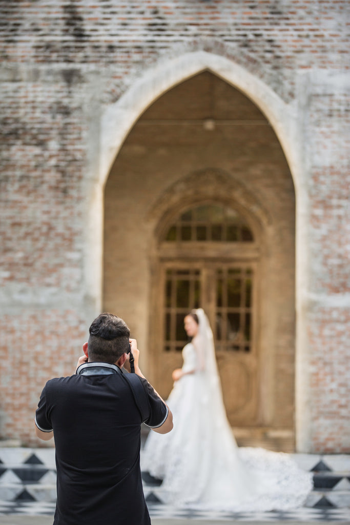 Beautiful bride being photographed by photographer on steps of cathedral