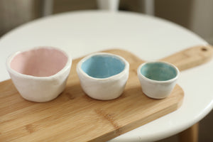 Three stacking pinch pots displayed on a bamboo bread board on a round table. Each one glazed externally glazed in white. Internally the largest is blush pink, the medium one is sky blue and the small one is teal. Handmade by Summer Freckles.