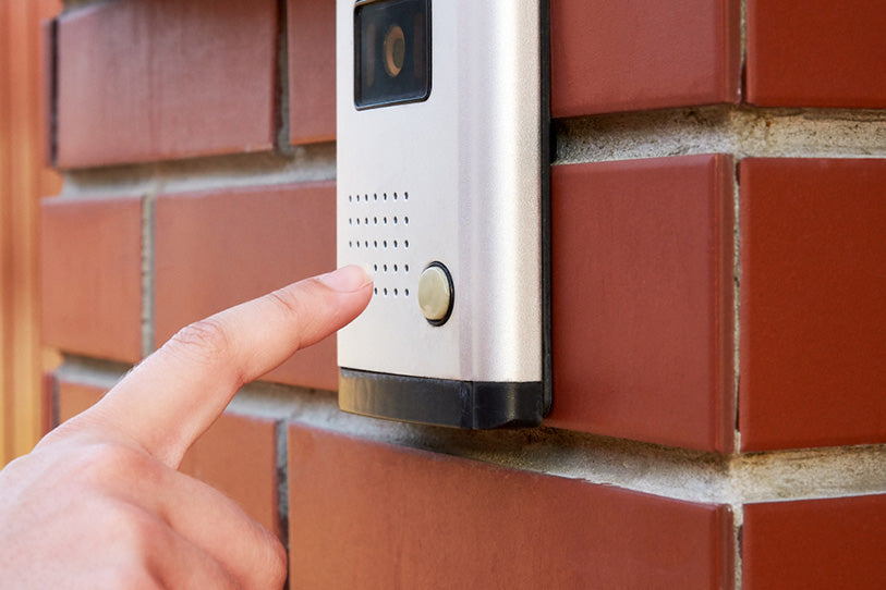 female hand presses button doorbell camera