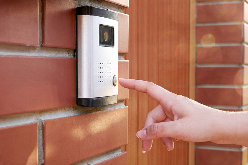 hand presses button for doorbell