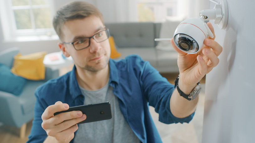 man adjusting indoor camera