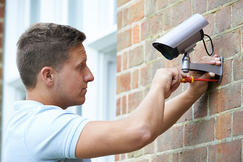 security consultant fitting camera to a house wall