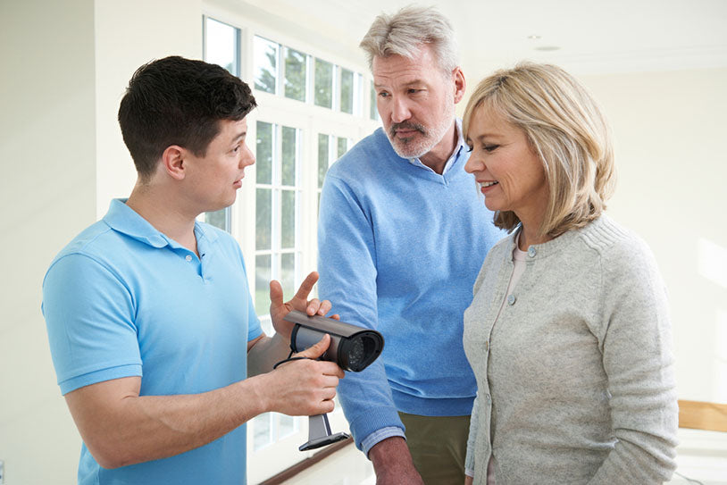 technician discussing camera with couple