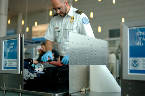 tsa agent searches luggage