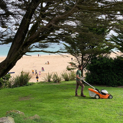 Man with a lawn mower cutting the grass in the foreground with some large trees in the mid ground and the white beach and bright blue sea in the background