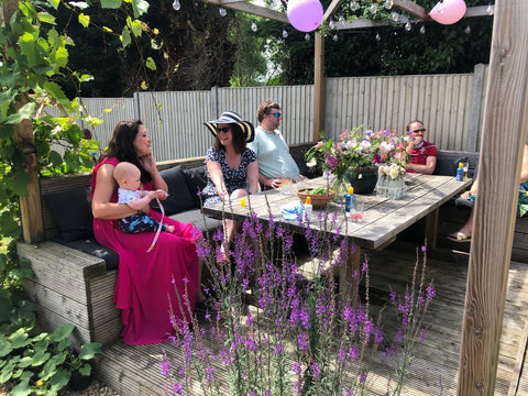 People sitting round a big wooden table under a grapevine growing over a pergola chatting
