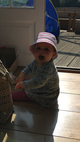 A 9 month old baby girl wearing a pink sun hat and laughing whilst playing with a handbag