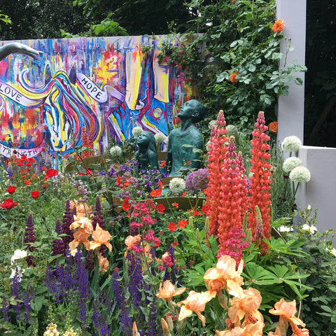 Red and purple lupins in front of a multicoloured piece of wall art at Chelsea flower show
