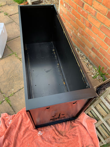 Empty black filing cabinet with the drawers removed on a stone patio next to a brick wall
