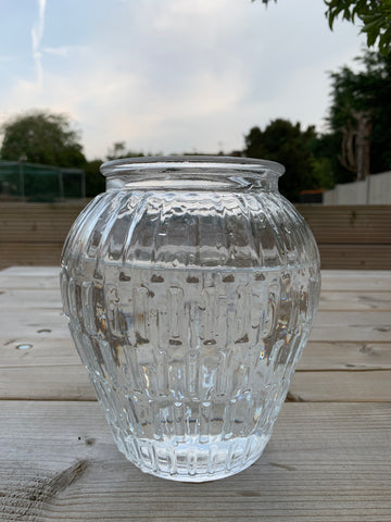 glass vase filled with water on top of a wooden table