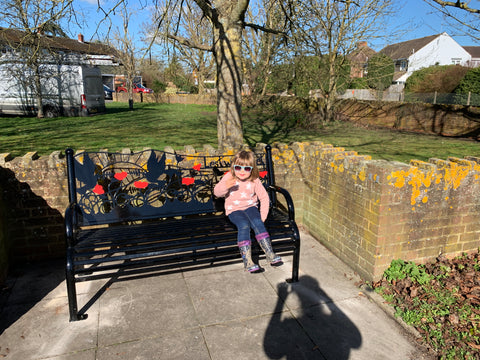 little girl sitting on a bench having a rest in the sunshine