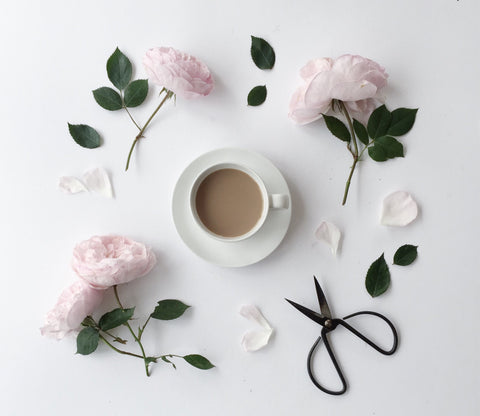 Pink roses surrounding a cup of tea in a white cup and saucer and some vintage floristry scissors