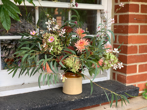 Windowsill flower arrangement containing hydrangea, dahlia, eucalyptus, sedum, gaura and japanese anemone