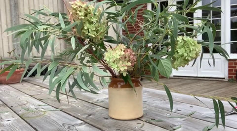 pickling jar containing eucalyptus and hydrangea flowers