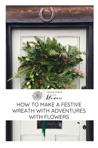 Pinterest image of a festive wreath on a olive green door of a cottage