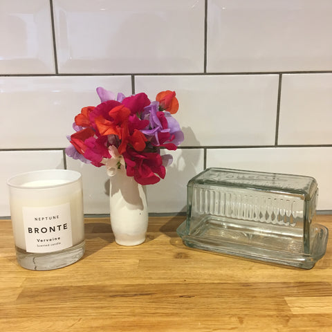small white vase of brightly coloured sweet peas in front of a white metro tiled wall along with a glass butter dish and a neptune candle.