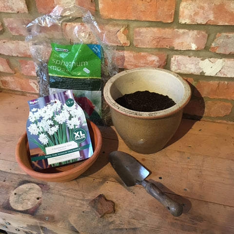 Equipment needed to create a paperwhite narcissus display- terracotta bowl, metal trowel, soil mixed with potting grit, a bag of moss and some crocks (broken pieces of pot)