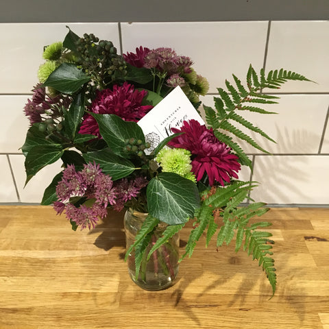 Posy of flowers in a glass jar including sheer purple chrysanthemums, froggy green chrysanthemums, pink astrantia, foraged ivy with berries and green fern leaves against a white metro tile background on top of a wooden worktop