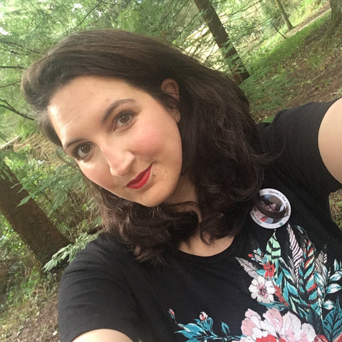 Smiling dark haired woman (me) wearing red lipstick and a black tshirt with a hand drawn floral and feather design on it in the middle of some woodland