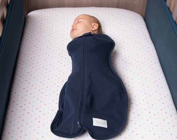 baby in navy woombie swaddle in cot