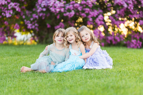 Three girls laugh together as they sit on the grass with purple lilac flowers behind them
