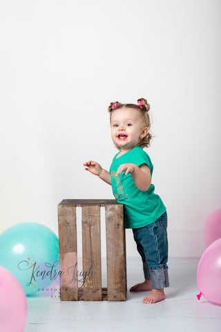 A little girl leans agains a crate and smiles on a white wood vinyl floor drop for her cake smash pictures