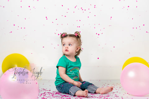 A little girl is showered in pink confetti with balloons on a white wood vinyl floor drop for her cake smash pictures