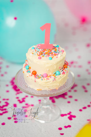 Cake smash cake surrounded by balloons and pink confetti on a white wooden vinyl photography backdrop