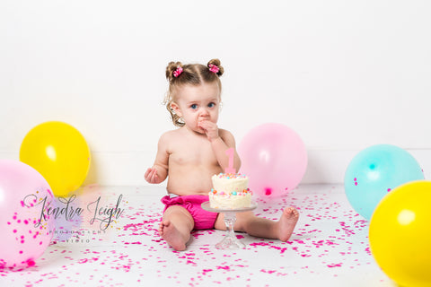 A little girl tries her cake at a cake smash photography session on a white wood vinyl backdrop
