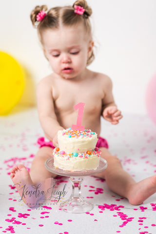 Little girl plays in frosting during her cake smash photo shoot on a vinyl photography floordrop of white wood