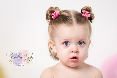 Little girl has her picture taken in a photography studio for her first birthday