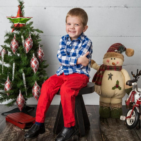 Young boy poses for a Christmas Mini Session in front of a white wood photography backdrop and Christmas decorations