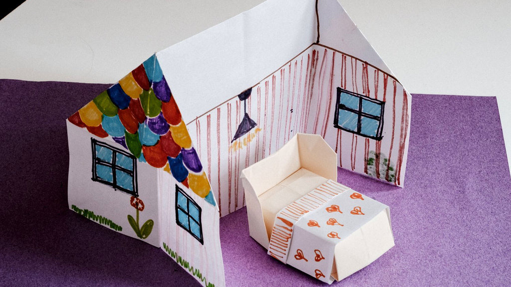 A fold-out origami house, with roof, windows and interior decor drawn and coloured in, and an origami bed in a photo for NiMi Projects origami workshops.