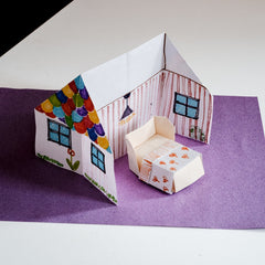 An origami house, decorated with color felt tip pens, and featuring an origami bed in a photo for NiMi Projects origami workshops.