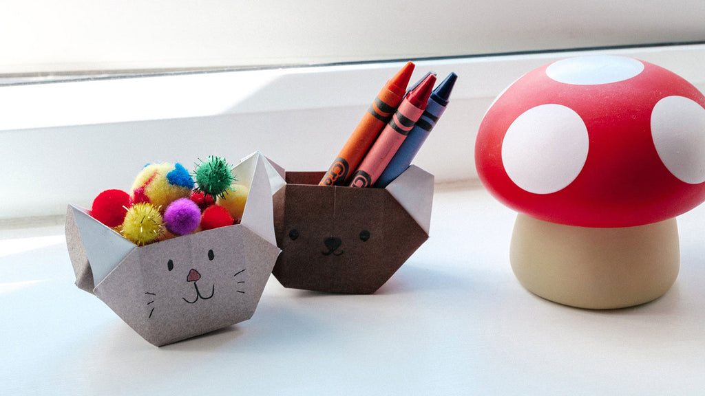 An origami koala head shaped box in grey filled with baubles and a brown cat head shaped box filled with crayons, displayed with a toadstool ornament in a photo for NiMi Projects origami workshops.