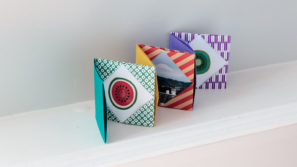 A multicolored and patterned mini origami concertina photo album with four sections, in an image for NiMi Projects origami workshops