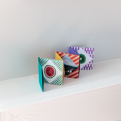 A multicolored and patterned origami concertina miniature photo album, displayed on a white background in a photo taken by NiMi Projects for its origami workshops.