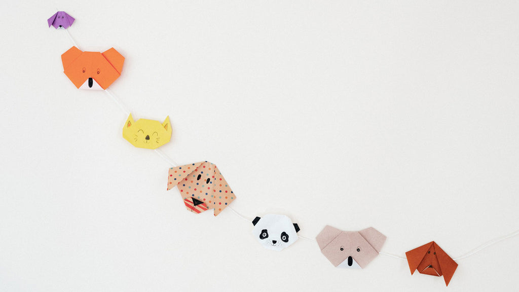 Multicolored animal bunting, featuring bear and dog faces, made for NiMi Projects origami workshops.
