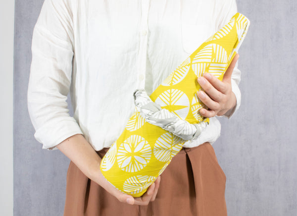 A woman holding a large bottle wrapped in a yellow and grey reversible patterned furoshiki wrapping cloth.