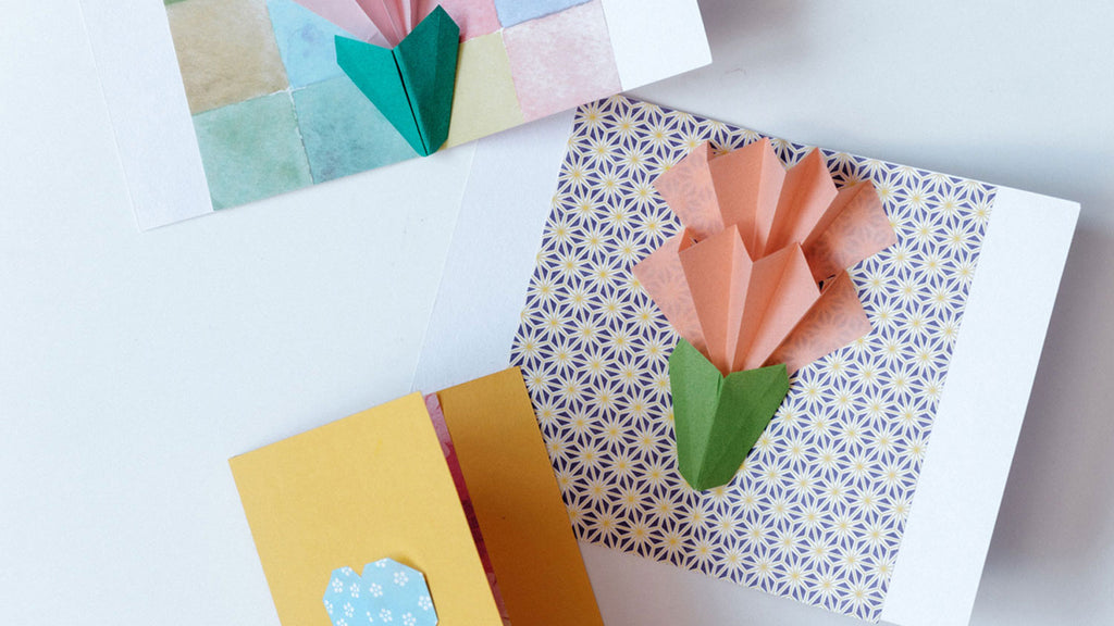 An origami popup card of a two-tiered orange carnation, with green bud, against a purple and green Japanese asanoha hemp patterned background. Photo by NiMi Projects origami workshops.