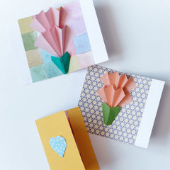 Three cards with popup two tiered flowers in pink and orange on patterned backgrounds in a photo for NiMi Projects origami workshops.